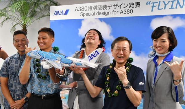 特別塗装のA380「FLYING HONU」の模型を手にシャカのポーズをとるANAの篠辺社長