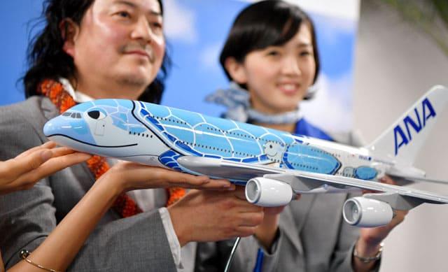 増岡さん(左)がデザインしたANAのA380特別塗装機「FLYING HONU」の模型