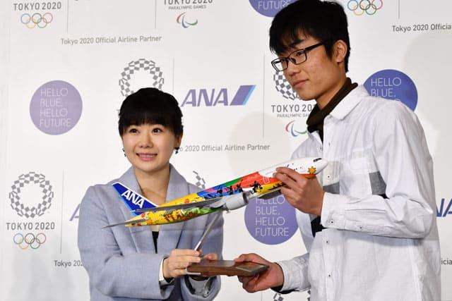 羽田空港の格納庫でHELLO 2020 JETをデザインした松本朝陽さん(右)にサイン入り模型を手渡す福原愛選手